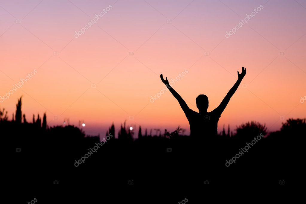 Silhouette of a man with arms raised at night  Stock Photo #6503958