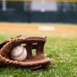 Old Baseball and Glove on Field - Stock Photo