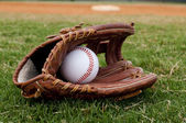 Baseball in Old Glove on Field — Stock Photo