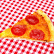 Pepperoni Pizza Slice on Red Gingham — Stock Photo #6365249