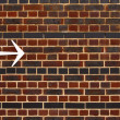 An arrow on a brick wall — Stok fotoğraf