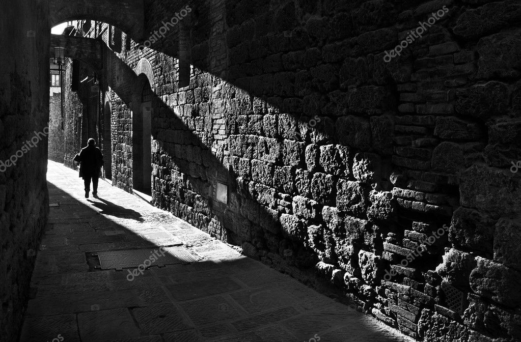 A pedestrian in a narrow medieval street in San Gimignano, Tuscany, Italy — Stock Photo #6320760