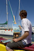 The artist paints on an easel at the yacht port — Stock fotografie