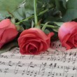 Stock Photo: Wilted rose flower on music paper