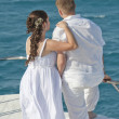 Newly married couple stood on the bow of a boat - ストック写真