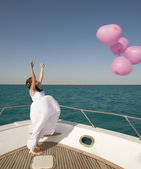 Bride releasing balloons from a boat — Stock Photo