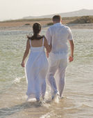 Young newlyweds walking on a tropical beach — Stock Photo