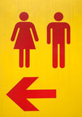 Yellow signs to the toilet with red arrow — 图库照片