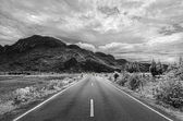 Black and white road to the mountain — Stock Photo