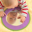 Baby boy plays with toy mirror — Stock Photo