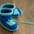 Knitted handmade baby's bootees on wood floor — Stock Photo