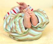 Cute baby foots in striped pants — Stock Photo