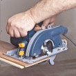 Carpenter with circular saw - Stock Photo