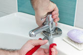 Plumber hands tightning water outlet with pliers — Stock Photo