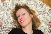 Young woman with her head lieing on the dollars — Stock Photo