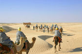 Tourists riding camels in Sahara desert — Stock Photo