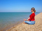 Girl in yoga position on an empty beach — Stock Photo