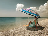 Filtered view of a girl, umbrella and beach — Stock Photo