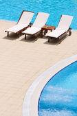 Sandalyeler yüzme havuzu yanında düzenlenen — Stok fotoğraf