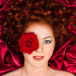 Red-haired woman with a flower on a background of curtains — Stock Photo