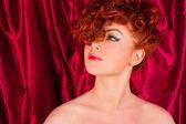 Rödhårig kvinna på en bakgrund av gardiner — Stockfoto