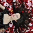 Beautiful brunette in red rose petals — Stock Photo