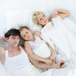 Happy family lying in bed — Stock Photo