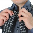 Businessman tying his tie - Stock Photo