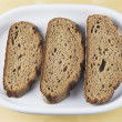 Three slices bread on a dish, drei Scheiden Brot auf einem Teller - Stock Photo