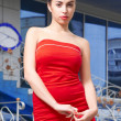 Beauty woman in red dress in the city at summer time — Stock Photo