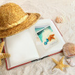 Book with straw hat and seashells in sand — Stock Photo #5483376