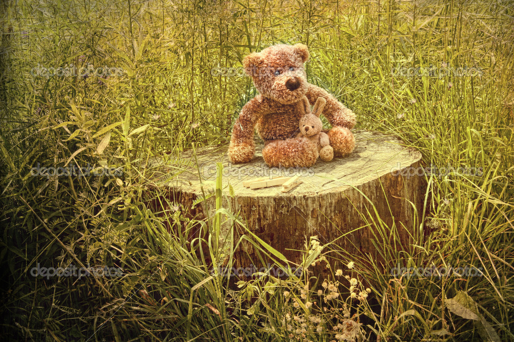 Small little bears on old wooden stump in grass — Stock Photo #5483373