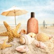 Suntan lotion and seashells on the beach — Stock Photo