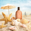 Suntan lotion and seashells on the beach - Stock Photo