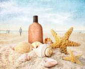 Zonnecrème en schelpen op het strand — Stockfoto