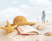 Straw hat , book and seashells in the sand — Photo