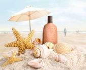 Suntan lotion and seashells on the beach — Stock Photo