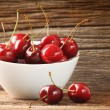 Red cherries in bowl on barn wood - Zdjęcie stockowe