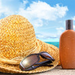 Beach items and suntan lotion at the beach - Stock Photo