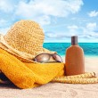 Suntan lotion, straw hat at the beach — Stock Photo