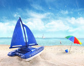 Toy sailboat in sand with beach scene — Stock Photo