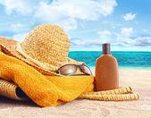 Suntan lotion, straw hat at the beach — Stock Photo