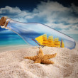 Ship in a bottle lying in the sand - Stock Photo