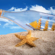 Ship in a bottle in a pile of sand - Stock Photo