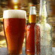 Stock Photo: Glass of beer with bottles