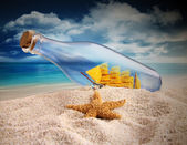 Ship in a bottle lying in the sand — Stock Photo