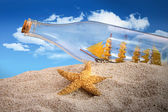 Ship in a bottle in a pile of sand — Stock Photo