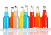 Bottles of multi-color drinks with ice on white — Stock Photo