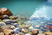 Closeup of rocks in water at lake Louise — Stock Photo
