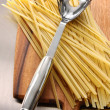 Fettuccine on wooden cutting board - Stock Photo